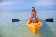 与他们的妈妈的两个孩子漂浮在的小船的 免版税库存照片