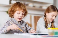 与他的姐妹的热情的有天才的儿童图画 免版税库存照片
