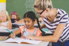 与他们的家庭作业的老师帮助的孩子在教室 免版税库存图片