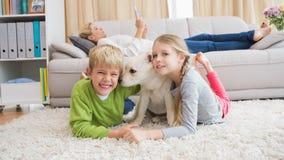 与他们的小狗的逗人喜爱的silblings在地毯 库存图片