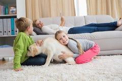 与他们的小狗的逗人喜爱的silblings在地毯 库存照片