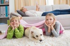 与他们的小狗的逗人喜爱的silblings在地毯 免版税库存图片