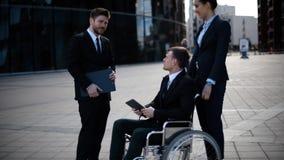 与他的工友和标志textpad docs的年轻残疾企业家商人谈话 股票视频