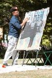 与他的手指的非裔美国人的艺术家油漆在艺术节 免版税库存图片