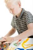 与他的手指的年轻白肤金发的男孩绘画 图库摄影