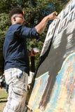与他的手指的年轻艺术家油漆在亚特兰大艺术节 免版税库存图片
