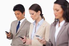 与他们的手机的年轻businessteam 免版税图库摄影