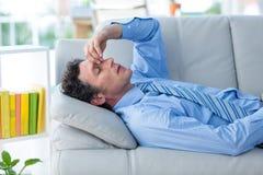 与头的担心的商人在说谎在长沙发的手上 免版税库存照片