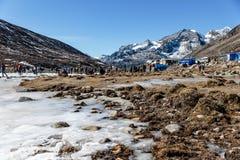 与冻结的池塘、雪、游人和市场的四轮驱动的汽车停车场与Yunthang谷在背景中在冬天 免版税图库摄影