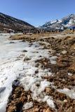 与冻结的池塘、雪、游人和市场的四轮驱动的汽车停车场与Yunthang谷在背景中在冬天 图库摄影