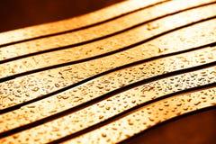 与轻的泄漏背景的日落钢长凳 库存照片