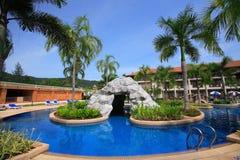 与洞穴的游泳池,在庭院旁边的太阳懒人和大厦 免版税库存图片