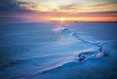 与冻结的湖、镇压和日落的冬天风景 免版税图库摄影