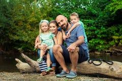 与他们的爱犬的年轻家庭,金毛猎犬 免版税图库摄影