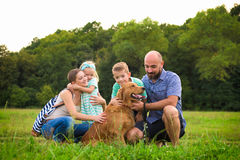 与他们的爱犬的年轻家庭,金毛猎犬 库存图片