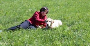与他的狗拉布拉多猎犬一起的年轻男孩 库存照片