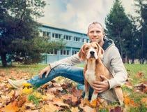 与他的狗的所有者在秋天步行在公园 库存照片