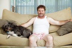 与他的狗的终日懒散在家的人 免版税库存照片