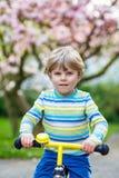 与他的第一辆自行车的小的小孩孩子男孩骑马 免版税图库摄影