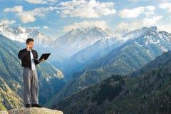 与他的膝上型计算机的年轻商人谈话由在mounta的电话 免版税库存图片