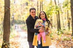 与他们的花费时间的女儿的愉快的年轻家庭室外在秋天公园 免版税库存图片