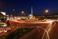 与轻的足迹的胜利纪念碑在街道上在曼谷 库存照片