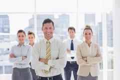 与他的队的微笑的英俊的商人 免版税图库摄影