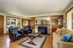 与黑皮革扶手椅子和壁炉的美国经典客厅内部 免版税库存照片