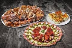 与满盘的开胃菜美味盘唾液在老破裂的片状庭院表上的烤猪肉和乳酪饼切片 免版税库存图片
