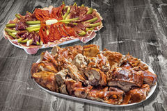 与满盘的开胃菜美味盘唾液在老破裂的片状木难看的东西背景的烤猪肉切片 免版税库存图片