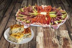 与满盘的开胃菜美味盘塞尔维亚传统Gibanica弄皱了在老破裂的木庭院表上设置的乳酪饼 免版税图库摄影
