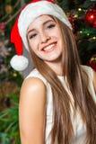 与黑眼睛、棕色头发和在家庆祝新年的圣诞老人帽子的年轻滑稽的美好的时装模特儿 新年装饰, wi 免版税库存照片