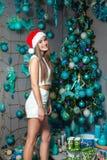 与黑眼睛、棕色头发和在家庆祝新年的圣诞老人帽子的年轻滑稽的美好的时装模特儿 新年装饰, wi 库存照片