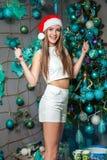 与黑眼睛、棕色头发和在家庆祝新年的圣诞老人帽子的年轻滑稽的美好的时装模特儿 新年装饰, wi 图库摄影