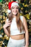 与黑眼睛、棕色头发和在家庆祝新年的圣诞老人帽子的年轻滑稽的美好的时装模特儿 新年装饰, wi 库存图片