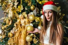 与黑眼睛、棕色头发和在家庆祝新年的圣诞老人帽子的年轻滑稽的美好的时装模特儿 新年装饰, wi 免版税库存图片