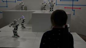 与滑稽的白色机器人的女孩舞蹈 股票视频