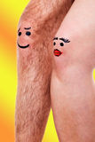 与滑稽的面孔的两个膝盖在黄色背景前面 库存照片