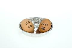 与滑稽的面孔的两个鸡蛋在卵形箔盘子,隔绝在白色背景 免版税库存图片
