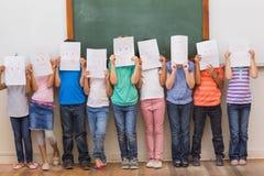 与滑稽的面孔的逗人喜爱的学生在教室 免版税库存图片