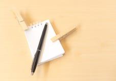 与黑笔和白色笔记薄的两晒衣夹 库存照片