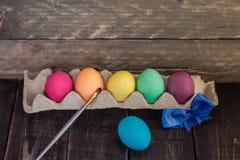 与画笔的五颜六色的手工制造复活节彩蛋在木桌上 库存照片
