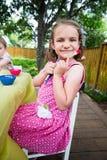 与画笔的愉快的小女孩姿势 库存图片