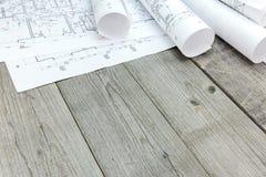 与建筑图纸的楼面布置图在木书桌上 免版税库存照片