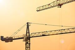 与建筑用起重机剪影的抽象工业背景在惊人的日落天空 免版税图库摄影