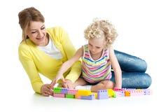 与建筑集合玩具一起的孩子和母亲戏剧 免版税库存照片