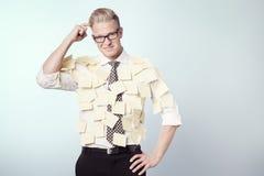 与贴纸的困惑的生意人附加他的衬衣。 库存图片