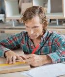 与统治者和铅笔的木匠测量的木头 免版税库存图片