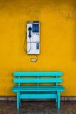 与细胞壁的古色古香的木椅子蓝色有黄色背景 免版税库存图片