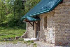 与绿色三角形屋顶的石农舍在绿色庭院背景  免版税库存图片